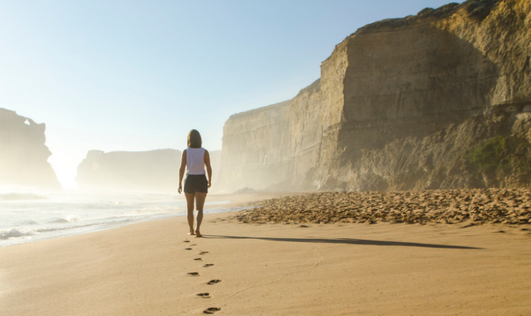 Person walking in the sand near the ocean, with cliffs in the background. The Alexander Technique helps us learn to move with freedom in any activity.